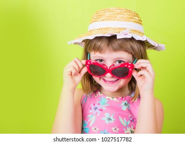 smiling little girl in straw hat and sunglasses