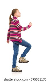 Smiling little girl in striped fleece jacket, jeans and hiking boots walking upstairs. Side view. Full length studio shot isolated on white.