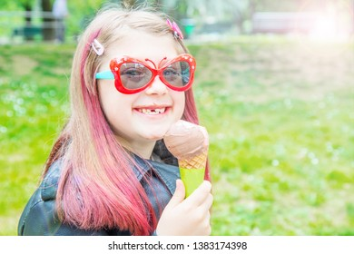 smiling little girl with sunglasses eating ice cream at the park