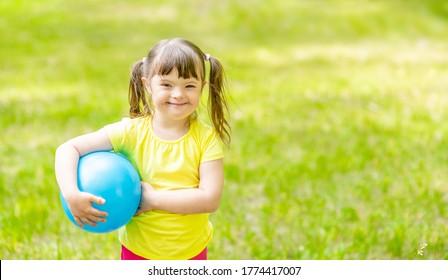 Lächelndes kleines Mädchen mit Syndrom hinunter hält Ball in einem Sommerpark. Leerzeichen für Text