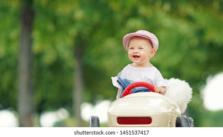 smiling little girl in toy car - summer day in park