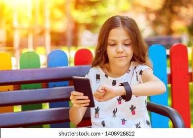 Smiling little girl using modern wearable smart watch and mobile phone outdoor synching data – happy kid with trendy gadgets synchronizing smartwatch with smartphone while sitting on bench in park