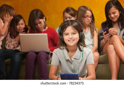 Smiling little girl with video game on a console with friends behind her