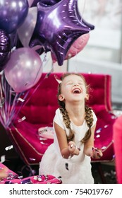 Smiling little girl in white dress plays with silver confetty standing before violet balloons