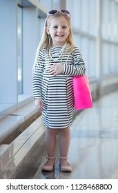 Smiling little girl in white striped dress with shopping bag