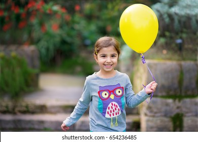 Smiling Little Girl with Yellow Balloon