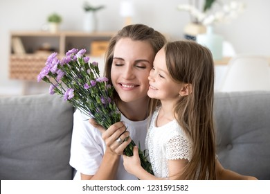 Smiling little kid daughter holding bouquet giving violet flowers congratulating happy mom with 8 march, cute preschool child girl making surprise to grateful mommy for birthday, mothers day concept