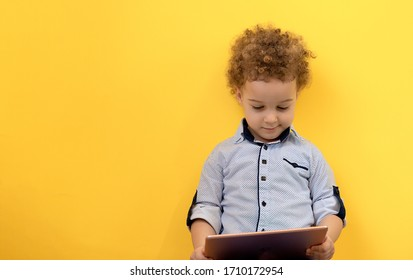 Smiling little kid looking at digital tablet and playing online games