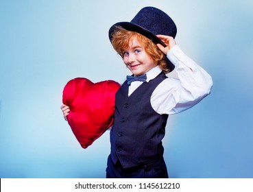 smiling little kid with red heart, boy actor in love, Valentine's day concept, love, happiness and people concept, stylishly dressed child plays a valentine with a red heart in his hands