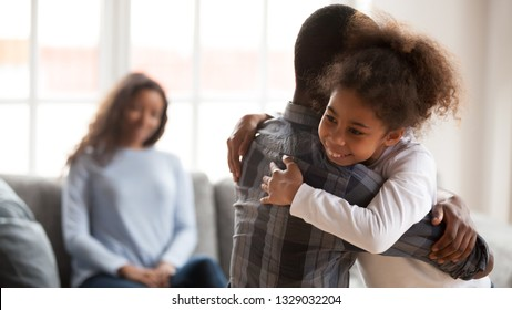 Smiling little mixed race girl hug young African American dad showing love and care, cute small happy daughter embrace father, parent hold kid in arms have close intimate moment together