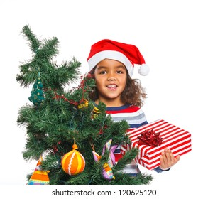 Smiling little mullato girl in Santa's hat with gift box and christmas tree, isolated on white