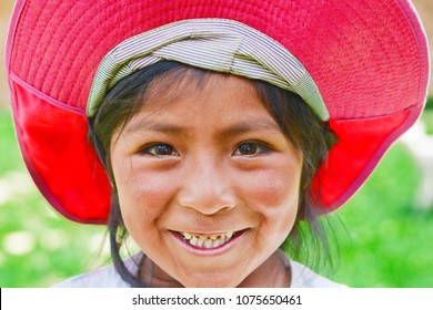 Smiling little native american girl wearing bright pink hat.