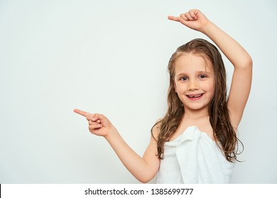 Smiling little preschool girl with wet hair photographed against white background wrapped in white towel pointing with finger towards empty space