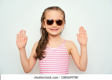 Smiling little preschool girl with wet hair photographed against white background wearing swimsuit and sunglasses demonstrates surrender gesture