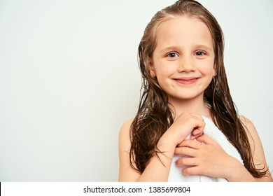 Smiling little preschool girl with wet hair photographed against white background wrapped in white towel