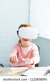 smiling little schoolchild using virtual reality headset while studying at home