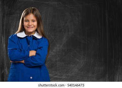 Smiling little student in front of a blackboard