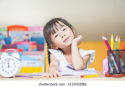 Smiling little student girl with many books at school. education and school concept