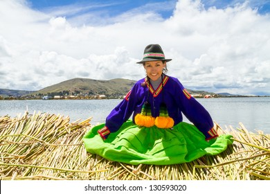 Smiling local girl Sitting on a floating Uros island on the shore of lake Titicaca