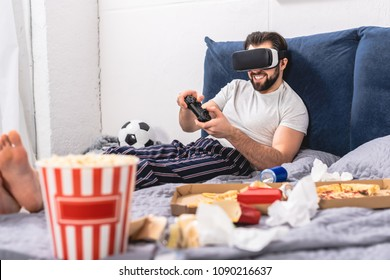 smiling loner using virtual reality headset and playing video game in bedroom