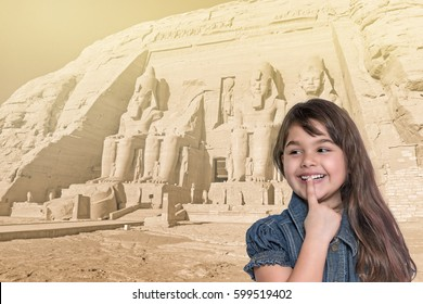 Smiling long haired tanned little girl with her finger over her mouth is standing in front of Abu Simbel temple in Egypt. Landmark in the background is edited as a vintage photo in sunlight.