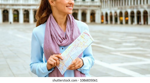 Smiling and looking into the distance, an elegant tourist holds a folded map in her hands. She knows that whatever path she takes, it will be an exciting and beautiful one, since she is in Venice.