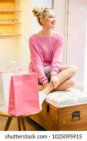 Smiling lovely fashionable woman in pink sweater relaxing, sitting on banquette in optician modern shop interior. Paper bag with purchases near her. Vertical portrait.Service and consumerism concept.