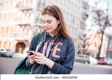 Smiling lovely young woman in earhones listening to music and using cell phone on the street of the city
