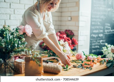 Smiling lovely young woman florist arranging plants in flower shop