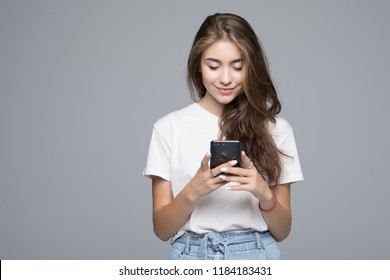 Smiling lovely young woman standing and using cell phone over grey background