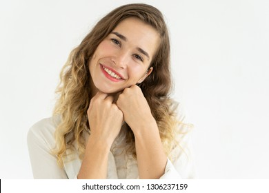 Smiling lovely young woman touching face with clasped hands. Lady looking at camera. Gratitude concept. Isolated front view on white background.