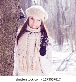Smiling Lovely Young Woman Winter Portrait at beautiful sunny winter day in the park. Happy Caucasian female wintertime season outdoor.