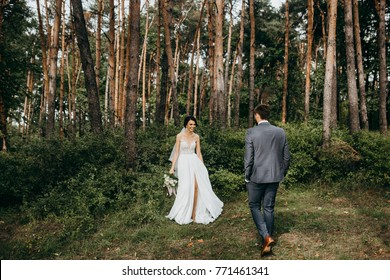 Smiling lovers in the forest on their wedding day