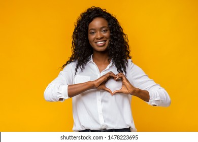 Smiling loving black woman shaping hands like heart on yellow background