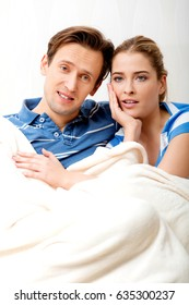 Smiling loving couple sitting on couch with blanket