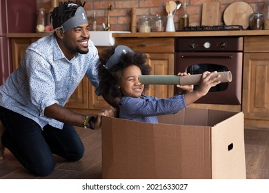 Smiling loving young African American father and small biracial daughter have fun play pirates sail in ship look in spyglass. Happy caring ethnic dad engaged in playful activity with teen girl child.