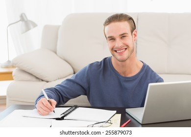 Smiling ma taking notes on notebook on white background