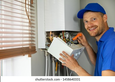 smiling maintenance and repair service engineer working with house gas heating boiler