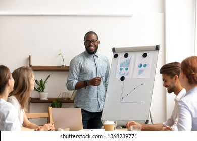 Smiling male african conference speaker give flipchart presentation explaining work result training sales team, black coach trainer mentor consulting clients interns at corporate group office seminar