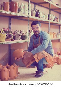 Smiling male artisan having ceramics in hands in ceramics workshop
