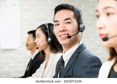 Smiling male Asian customer service telemarketing agent working in call center with team