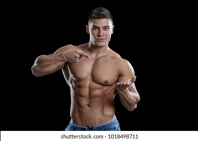 A smiling male bodybuilder points to his open palm. The picture is suitable for advertising sports goods and services. Isolated in black background.