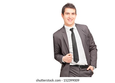 Smiling male businessman leaning against wall isolated on white background