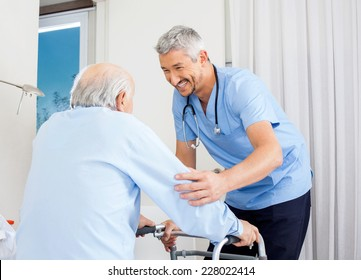 Smiling male caretaker helping senior man to use walking frame in bedroom at nursing home