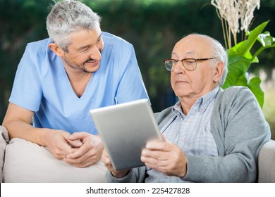 Smiling male caretaker looking at senior man using tablet computer at nursing home porch