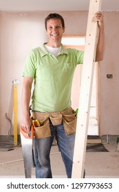Smiling male carpenter holding timber plank at camera