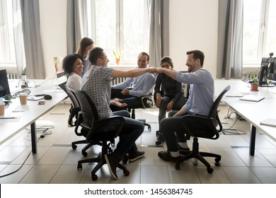 Smiling male colleagues involved in group teambuilding activity join hands motivated for shared goal, happy coworkers give fists bump greeting at meeting or congratulating with achieved success