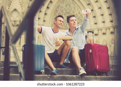 Smiling male couple with luggage doing selfie and sitting in city
