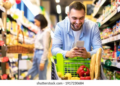 Smiling Male Customer Doing Grocery Shopping Using Smartphone Walking With Cart In Supermarket. Selective Focus. Man Using Groceries Shopping Application On Phone Bying Food In Super Market