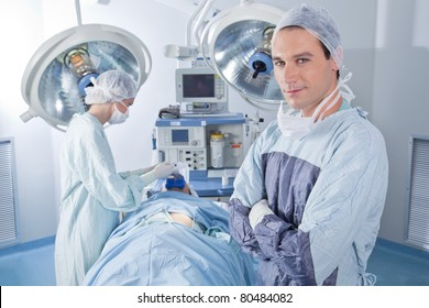 Smiling male doctor with arms crossed in operating room
